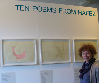 Jila Peacock in front of some of her shape poems